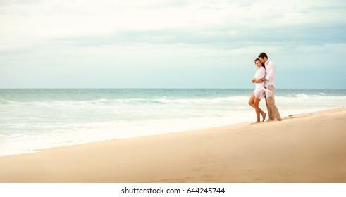 Couple embracing on beach, romantic feelings, honeymoon concept