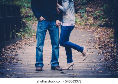Couple embracing on wooden bridge outdoors in a forest.