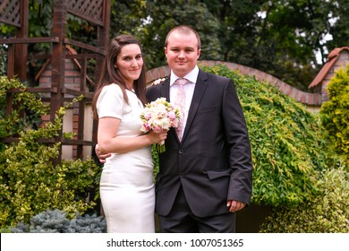 couple embracing in park with colored bouquet of flowers