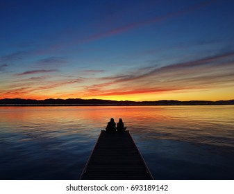 Couple at the end of a pier (couple & pier in silhouette) enjoying a spectacular orange, red & blue sunset behind Adirondack Mountains at Lake Champlain in Burlington, Vermont to end a nice autumn day