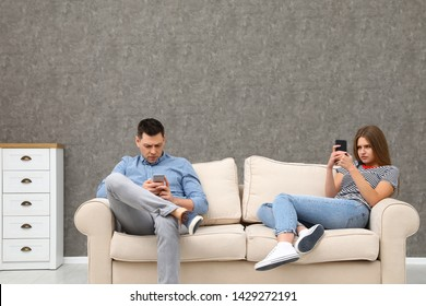 Couple engaged in smartphones while spending time together at home. Loneliness concept