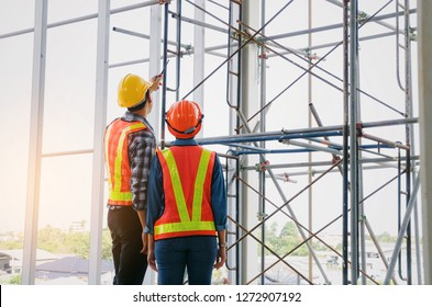 couple of engineer or technician man and woman with safety helmet holding mobile radio phone planning about building plan to greeting start up project in construction site building, industry concept