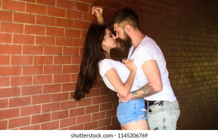 Couple enjoy intimacy without witnesses public place. Girl and hipster full of desire cuddling. Couple in love full of desire brick wall background. No rules for them. Couple find place to be alone.