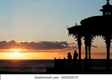 A couple enjoy a stunning sunset at the Bandstand on Brighton and Hove's seafront. The Bandstand first opened in 1884 and is considered to be one of the finest examples of a Victorian bandstand
