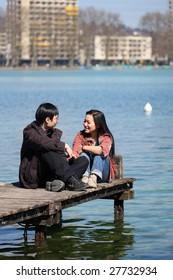 couple enjoy the sunshine beside lake