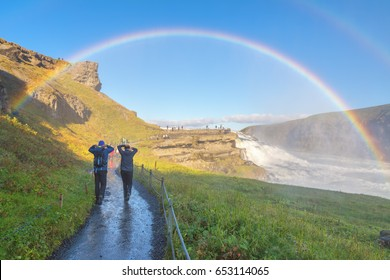 A couple enjoying the amazing Gullfoss waterfall with rainbow, Iceland
