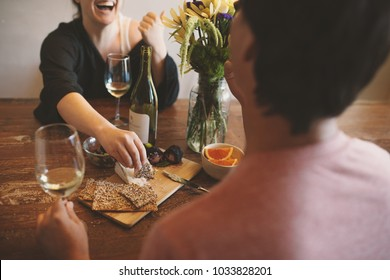 couple enjoying appetizers and wine on rustic wood table