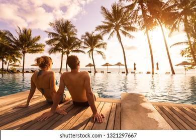 Ferien am Strand mit Swimmingpool und Kokospalmen in der Nähe der Küste mit schöner Landschaft bei Sonnenuntergang, Flitterwochen Ziel