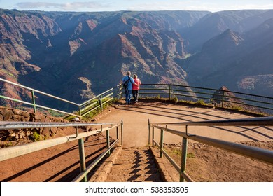 """A couple enjoying the beautiful views of the Waimea Canyon lookout also known as the """"Grand Canyon of Kauai"""" with vog (haze containing volcanic dust, gases)"""