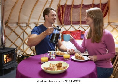 Couple Enjoying Breakfast Whilst Camping In Traditional Yurt