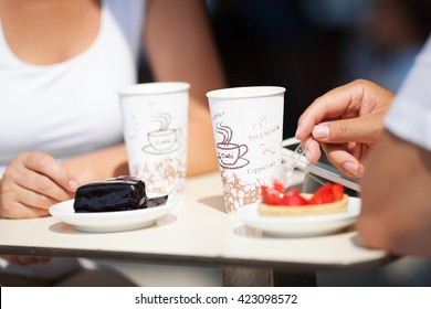 Couple enjoying coffee and cake at a cafeteria with a low angle view of the chocolate and strawberry cakes and disposable coffee cups