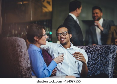 Couple enjoying a glass of champagne after work together at a bar.