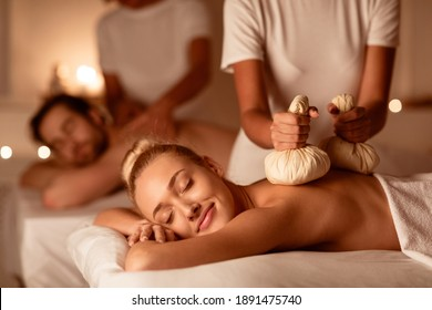 Couple Enjoying Herbal Massage. Relaxed Husband And Wife At Exotic Spa Resort, Lying With Eyes Closed Receiving Thai Massage With Aromatic Bags. Body Beauty Treatment, Relaxation And Wellness
