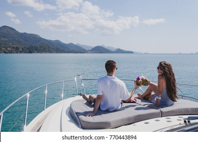 couple enjoying honeymoon onboard of luxury boat, luxurious yacht in tropical sea, man and woman drinking coconuts and relax