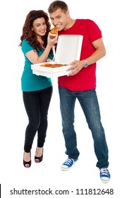 Couple enjoying pizza together, great bonding. Full length shots