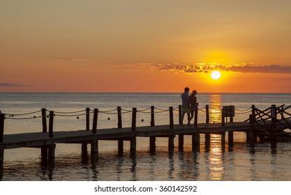 couple enjoying romantic walk on pier by ocean during sunset