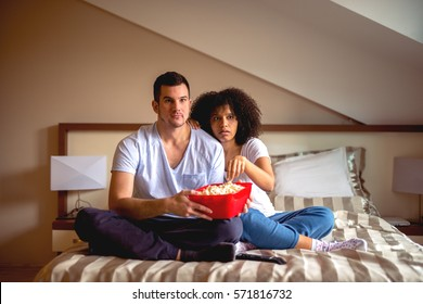 Couple enjoying sharing time at home with movie and popcorn.