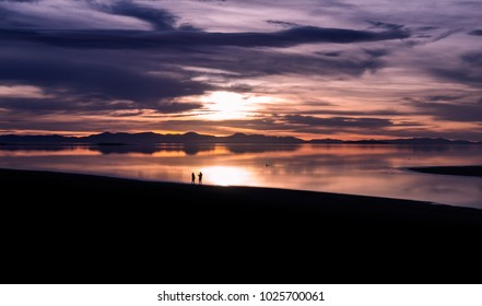 A couple enjoying the sunset at Antelope Island in winter. They were having fun taking pictures together and enjoying each others company.