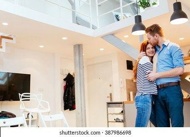 Couple enjoying their new luxurious home and hugging in living room
