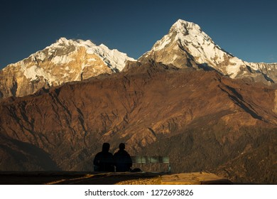 Couple enjoying view of Annapurna South from Poon Hill. Himalaya Mountains, Nepal.