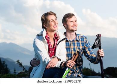Couple enjoying view hiking in the alpine mountains