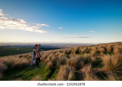Couple enjoys beautiful bushes  Christchurch city view in New Zealand. Romantic couple goes on dating. A pair of couple goes on honeymoon in natural landscape. Happiness image of a young couple.