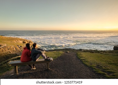 Couple enjoys beautiful coastal scenery near Dunedin in New Zealand. Romantic couple goes on holiday. A pair of couple goes on honeymoon in natural landscape. Happiness image of a young couple.
