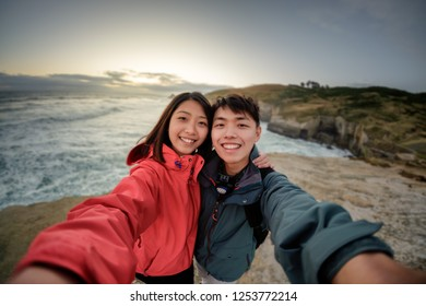 Couple enjoys beautiful coastal scenery near Dunedin in New Zealand. Romantic couple takes selfie together. A pair of couple goes on honeymoon in natural landscape. Happiness image of a young couple.