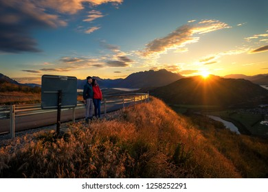 Couple enjoys beautiful queenstown scenery in New Zealand. Romantic couple goes on road trip. A pair of couple goes on honeymoon in natural landscape. Happiness image of a young couple.