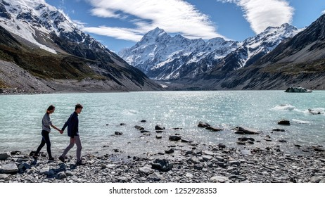 Couple enjoys beautiful scenery in New Zealand. Romantic couple holding hands. A pair of couple goes on honeymoon in natural landscape. Happiness image of a young couple exploring mount cook.