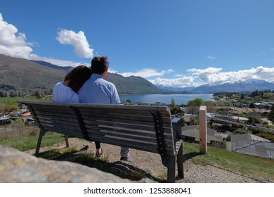 Couple enjoys beautiful wanaka scenery in South Island in New Zealand. Romantic couple goes on holiday. A pair of couple goes on honeymoon in natural landscape. Happiness image of a young couple.