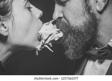 Couple enjoys meal, meat or fowl. Man and woman with chickens skeleton in mouths on black background. Couple eats chicken together. Enjoy your meal concept. Weird aesthetics, closeness and intimacy.