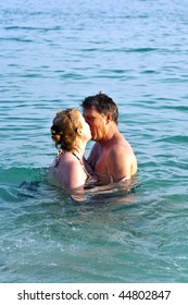 couple enjoys the romantic clear warm salt water in the sea and like to kiss