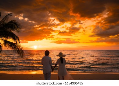 Couple enjoys their vacation time.on beautiful sunset at the beach, together is feel happiness.