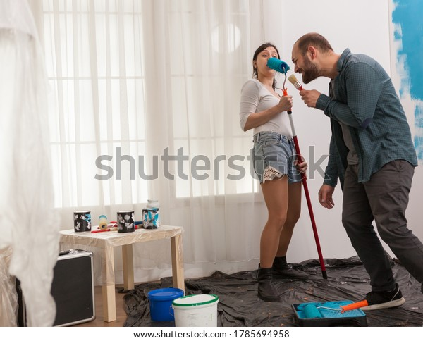 Couple excitement during home repair singing and dancing. Apartment redecoration and home construction while renovating and improving. Repair and decorating.