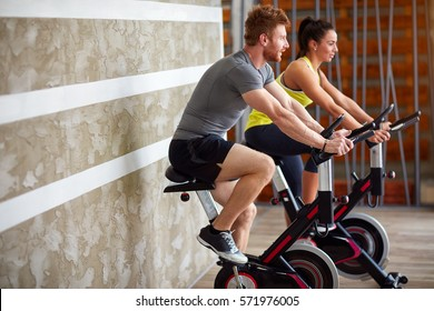 Couple exercises legs on bike in gym