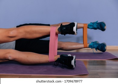 Couple exercising doing workout for legs with elastic bands lying on floor in gym.