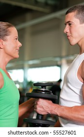 Couple exercising with dumbbells in a gym