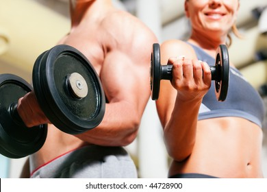 Couple exercising with dumbbells in a gym, focus on the weights, only torso of man and woman to be seen