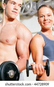 Couple exercising with dumbbells in a gym, focus on eyes of man and woman