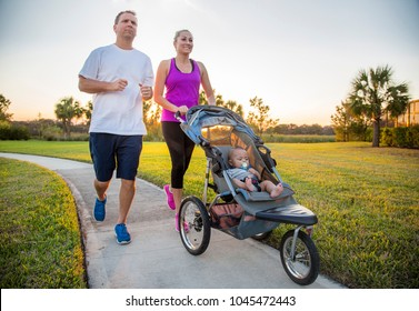 Couple exercising and jogging together at the park pushing their baby in a stroller