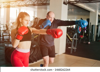 Couple exercising punching. Young woman and man training punches in boxing gloves at the gym.
