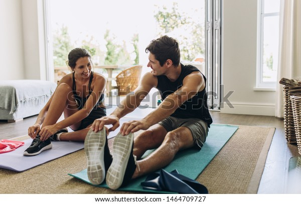 Couple exercising together. Man and woman in sports wear doing workout at home.