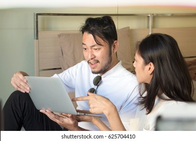 Couple is exiting with business on line. They are working from home in their bedroom