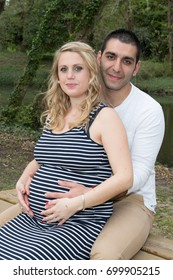 Couple Expecting Pregnancy Woman Hugging and Kissing Outdoor