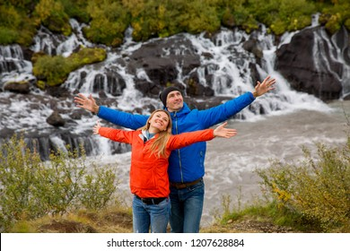 Couple explore beautiful place in Iceland. Hraunfossar waterfall