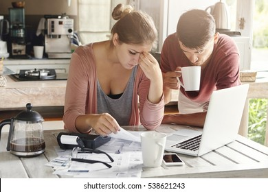 Couple facing financial problem, failing to pay loan in bank. Stressed woman managing family budget, making calculations using laptop and calculator, her husband standing next to her with cup of tea