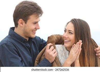Couple falling in love with he covering her with his jacket in a cold winter outdoors