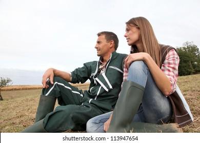 Couple of farmers sitting outside in field