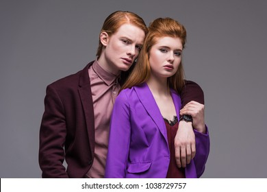 Couple of fashion models in formal wear isolated on grey